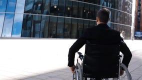 Hombre de negocios inválido en movimiento de la silla de ruedas cerca del centro de negocio moderno almacen de video