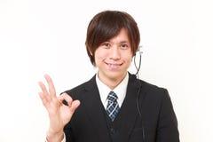 Hombre de negocios japonés joven del centro de atención telefónica que muestra la muestra perfecta Imagenes de archivo