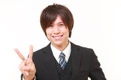 Hombre de negocios japonés joven que muestra una muestra de la victoria Fotos de archivo
