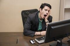 Hombre de negocios joven aburrido cansado que se sienta en oficina Foto de archivo libre de regalías