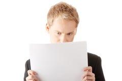 Hombre de negocios joven acertado que lee la tarjeta en blanco Fotografía de archivo libre de regalías