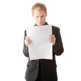 Hombre de negocios joven acertado que lee la tarjeta en blanco Imagenes de archivo