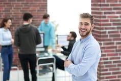 Hombre de negocios joven acertado que se coloca con sus colegas en b Fotografía de archivo libre de regalías