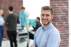Hombre de negocios joven acertado que se coloca con sus colegas en b Fotos de archivo