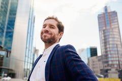 Hombre de negocios joven acertado que sonríe con confianza mientras que se coloca en la ciudad Imágenes de archivo libres de regalías
