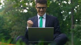 Hombre de negocios joven acertado que trabaja afuera, sentándose en hierba, trabajo eficaz almacen de video