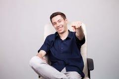 Hombre de negocios joven acertado sonriente feliz en la camisa azul casual que se sienta en una silla de la oficina Fotografía de archivo libre de regalías