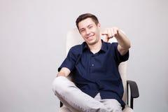 Hombre de negocios joven acertado sonriente feliz en la camisa azul casual que se sienta en una silla de la oficina Imagen de archivo