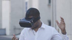 Hombre de negocios joven afroamericano en la camisa blanca usando casco de la realidad virtual en la ciudad outdoor metrajes