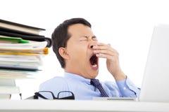 Hombre de negocios joven agotado que bosteza en el trabajo Imagen de archivo libre de regalías