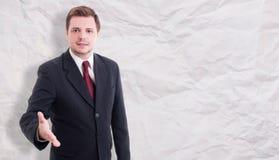 Hombre de negocios joven agradable que hace gesto que da la bienvenida Imagen de archivo