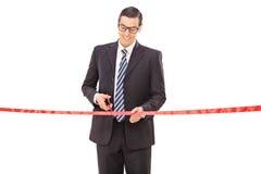 Hombre de negocios joven alegre que corta una cinta roja Imagenes de archivo