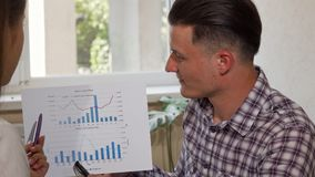 Hombre de negocios joven alegre que explica a su colega su carta de negocio metrajes