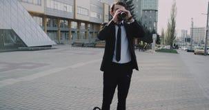 Hombre de negocios joven antes de comenzar el suyo día del trabajo a tomar su café delante del edificio de oficinas moderno metrajes
