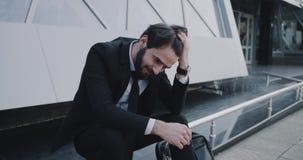 Hombre de negocios joven antes de que la entrevista consiga en la tensión, sentándose delante del edificio de la oficina de negoc almacen de video