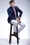 Hombre de negocios joven asentado con la expresión seria Imagen de archivo