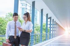 Hombre de negocios joven asiático, mujer que celebra reuniones de la charla del teléfono móvil los procesos del anuncio publicita fotos de archivo libres de regalías