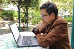 Hombre de negocios joven asiático que mira el ordenador portátil y el pensamiento de la pantalla foto de archivo