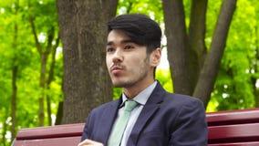 Hombre de negocios joven asiático que se sienta en parque y que come las patatas fritas almacen de video