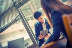 Hombre de negocios joven de Asia en oficina usando la tableta fotos de archivo libres de regalías