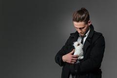 Hombre de negocios joven atractivo que coloca y que sostiene el conejo fotografía de archivo