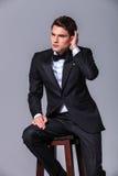 Hombre de negocios joven atractivo que fija su pelo fotos de archivo