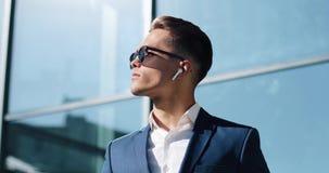 Hombre de negocios joven atractivo usando los auriculares inalámbricos que se colocan afuera Él gafas de sol que llevan y miradas almacen de video