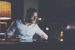 Hombre de negocios joven barbudo en las lentes que trabajan en la oficina en la noche Hombre que usa la computadora portátil Hori Fotografía de archivo