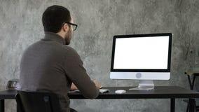 Hombre de negocios joven barbudo woking en el ordenador Visualización blanca almacen de metraje de vídeo