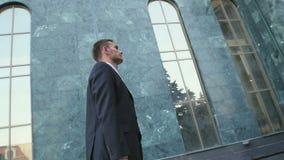 Hombre de negocios joven, bien parecido enviado al edificio de oficinas almacen de video