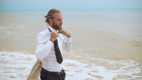 Hombre de negocios joven cabelludo rubio que afloja el lazo y que lo lanza hacia fuera cerca de la playa en la cámara lenta almacen de metraje de vídeo