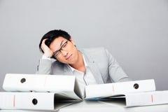 Hombre de negocios joven cansado que se sienta en la tabla foto de archivo libre de regalías