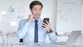Hombre de negocios joven Celebrating Success en Smartphone almacen de video