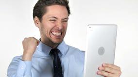 Hombre de negocios joven Celebrating Success mientras que usando la tableta en el fondo blanco almacen de video