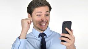 Hombre de negocios joven Celebrating Success mientras que usando Smartphone en el fondo blanco almacen de metraje de vídeo
