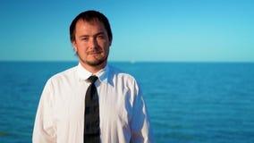 Hombre de negocios joven cerca del mar azul almacen de video
