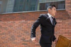 Hombre de negocios joven chino que corre en una calle de la ciudad Imagen de archivo
