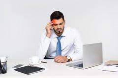 hombre de negocios joven con exceso de trabajo que sufre de dolor de cabeza mientras que se sienta Imagen de archivo