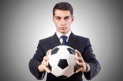 Hombre de negocios joven con fútbol en el blanco Foto de archivo libre de regalías