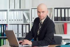 Hombre de negocios joven con la cabeza calva en la oficina Fotos de archivo