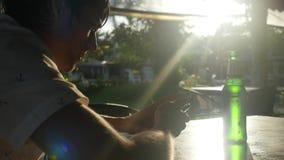 Hombre de negocios joven con la cerveza de consumición del smartphone en café al aire libre durante puesta del sol con efectos as imagenes de archivo