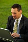 Hombre de negocios joven con la computadora portátil Imagen de archivo libre de regalías