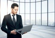 Hombre de negocios joven con la computadora portátil Fotos de archivo