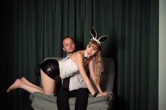 Hombre de negocios joven con la mujer atractiva en traje del conejito Foto de archivo