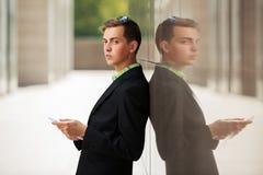 Hombre de negocios joven con la tableta en la pared Fotografía de archivo libre de regalías