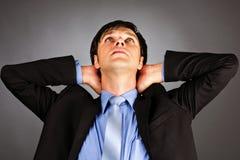 Hombre de negocios joven con los brazos cruzados detrás de la cabeza Fotografía de archivo