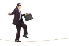 Hombre de negocios joven con los ojos vendados que camina en cuerda Foto de archivo libre de regalías