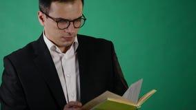 Hombre de negocios joven con los vidrios que lee un libro en backgraund verde metrajes
