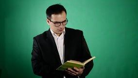 Hombre de negocios joven con los vidrios que lee un libro en backgraund verde almacen de video