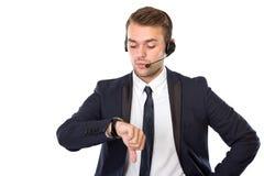 Hombre de negocios joven con un auricular que mira el suyo relojes Fotos de archivo